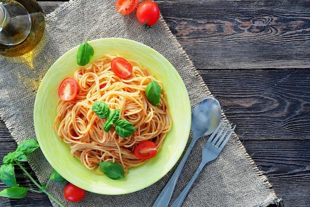Espaguete em molho de tomate com tomate fresco, manjericão verde e azeite de oliva Foto Premium
