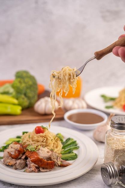 Espaguete em um prato com tomate coentro e manjericão. Foto gratuita