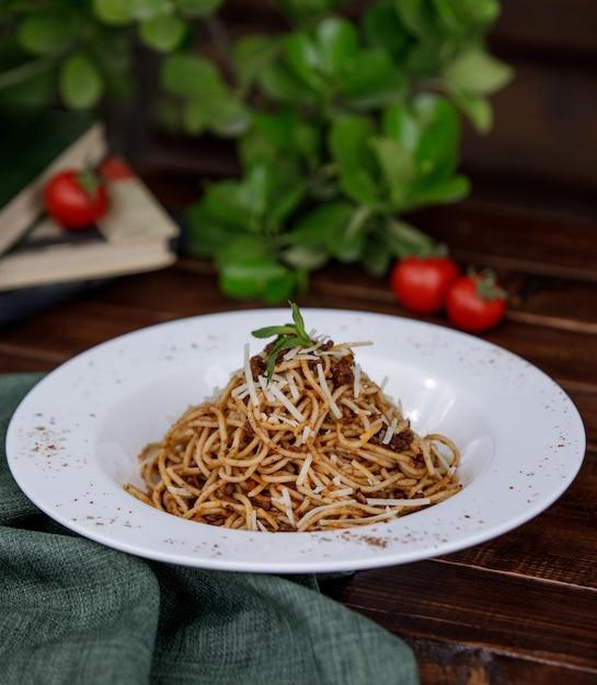 Espaguete italiano com folhas de hortelã no topo dentro de um prato de tigela Foto gratuita