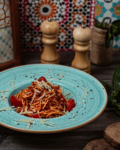 Espaguete italiano em molho de tomate com folhas de hortelã na parte superior dentro de um prato de tigela azul Foto gratuita