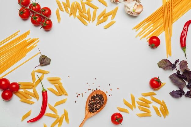 Espaguetes da massa com os ingredientes para cozinhar a massa em um fundo branco, vista superior. Foto Premium