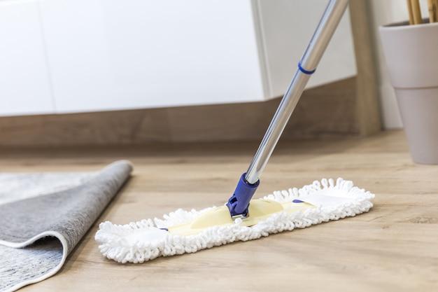 Espanador branco moderno sendo usado para limpeza de um piso de madeira Foto Premium