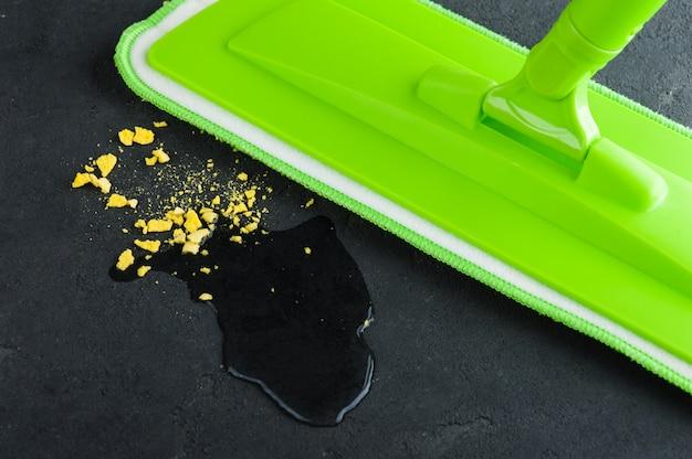 Espanador verde esfregando o chão de concreto preto Foto Premium
