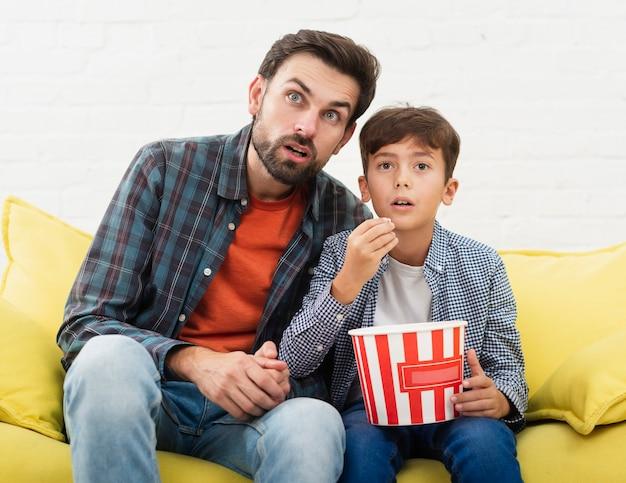 Espantado pai e filho assistindo tv Foto gratuita