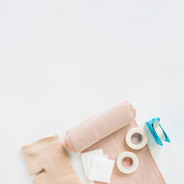 Esparadrapo; bandagem médica e cinta de joelho em fundo branco Foto gratuita