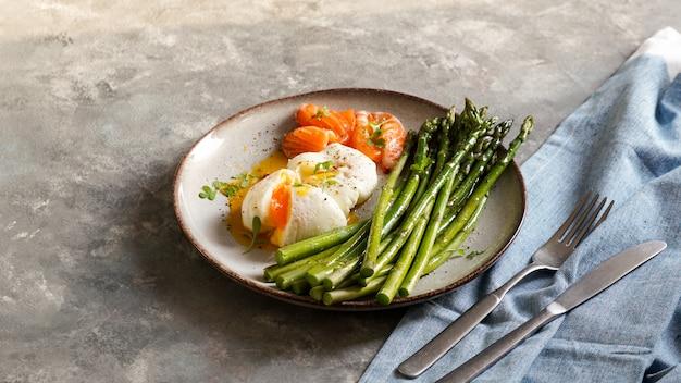 Espargos com ovos escalfados ans salgados salmão. saboroso café da manhã saudável Foto Premium