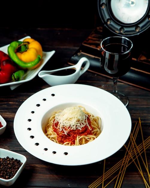 Esparguete à bolonhesa com vinho tinto na mesa Foto gratuita