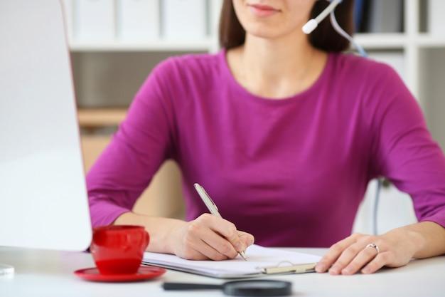 Especialista em call center mulher recebe pedidos por telefone e escreve em um notebook, com profundidade de campo Foto Premium