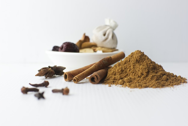 Especiarias, canela, canela em pó, syzygium aromaticum, illicium verum, cardamomo e especiarias no prato Foto Premium