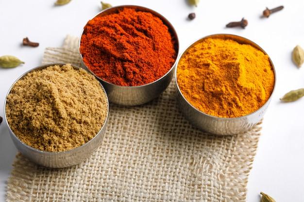 Especiarias coloridas indianas vermelho pimenta em pó, pó de cúrcuma, coentro em pó na mesa branca Foto Premium
