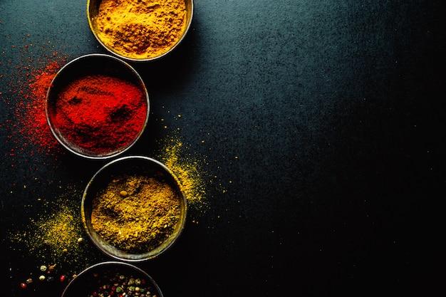 Especiarias coloridas na mesa escura, copyspace Foto gratuita