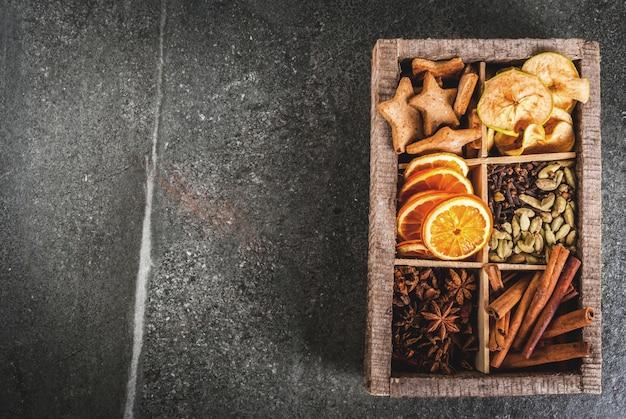 Especiarias de natal para assar, coquetéis, vinho quente, com biscoitos de gengibre (estrelas) - maçã seca, laranja, cardamomo, cravo, canela, anis. caixa de madeira velha, mesa de pedra preta. copie o espaço vista superior Foto Premium