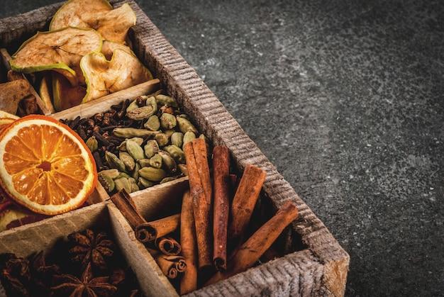 Especiarias de natal para assar, coquetéis, vinho quente, com biscoitos de gengibre (estrelas) - maçã seca, laranja, cardamomo, cravo, canela, anis. caixa de madeira velha, mesa de pedra preta. copie o espaço Foto Premium