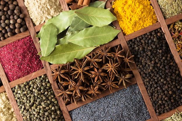 Especiarias e ervas em caixas de madeira. condimentos multicoloridos Foto Premium