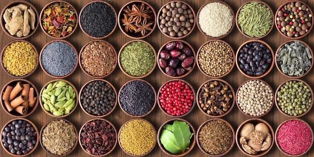 Especiarias e ervas em xícaras. temperos coloridos papel de parede Foto Premium