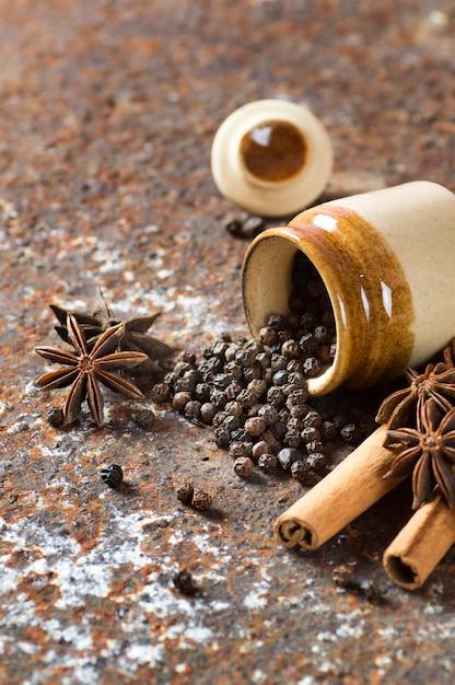 Especiarias e ervas. ingredientes alimentares e gastronômicos. paus de canela, estrelas de anis, pimenta preta Foto Premium