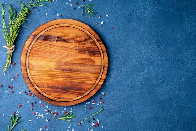 Especiarias, ervas e tábua de madeira redonda sobre fundo azul escuro de concreto preto. topo Foto Premium