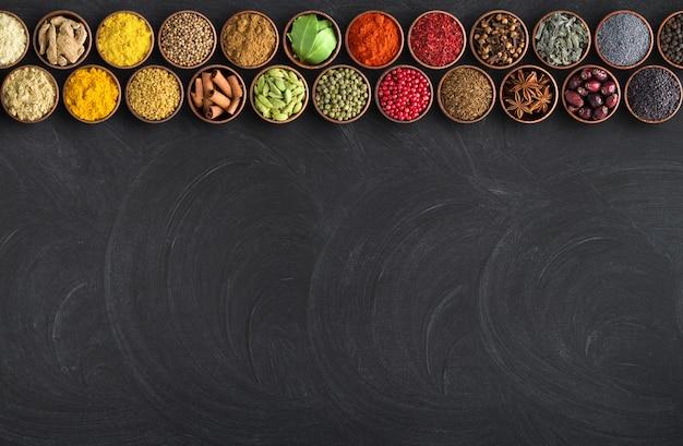 Especiarias indianas em fundo preto tabela. quadro para comida com condimentos Foto Premium