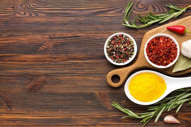 Especiarias na colher e tigelas na mesa de madeira Foto gratuita