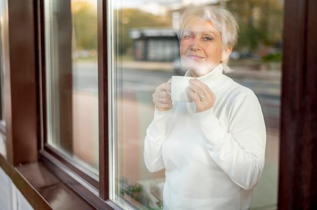 Espelhar o café bebendo fêmea sênior Foto gratuita