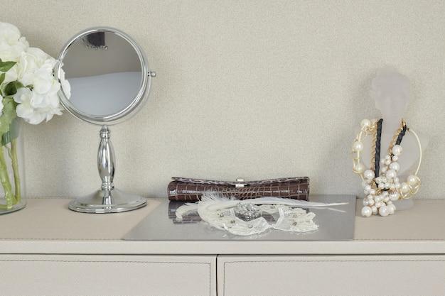 Espelho, jóias e maquiagem em uma mesa Foto Premium
