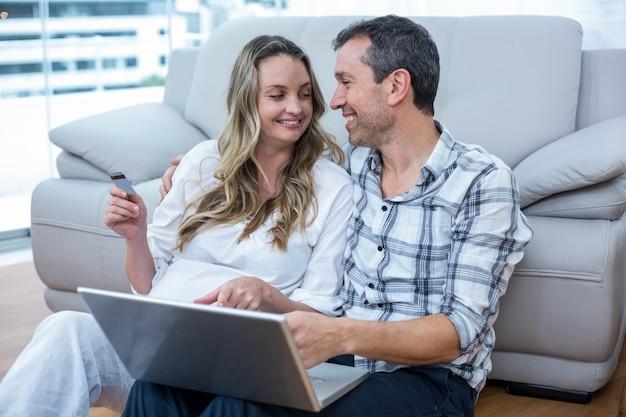 Esperando casal sentado no chão e usando o laptop Foto Premium