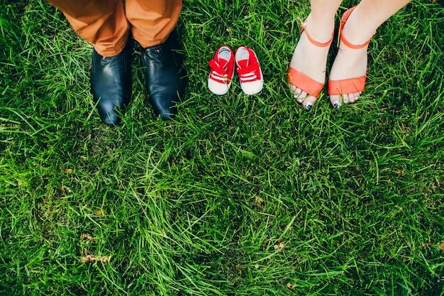 Esperando por um milagre. sapatos para adultos e crianças. sapatos infantis na grama entre as pernas dos pais. Foto Premium