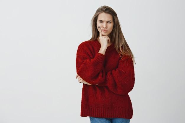 Espere um segundo. namorada sexy encantadora mal-humorada perplexa com suéter solto vermelho fazendo beicinho, franzindo a testa, focada e pensativa, tocando o rosto, apertando os olhos com descrença e dúvida, tendo um sentimento suspeito Foto gratuita