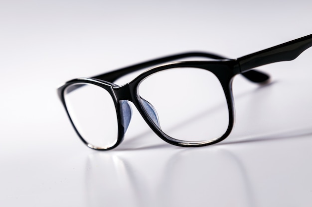 Espetáculos dos vidros do olho roxo com quadro preto brilhante para ler a vida diária a uma pessoa com deficiência visual isolaged no fundo branco. Foto Premium