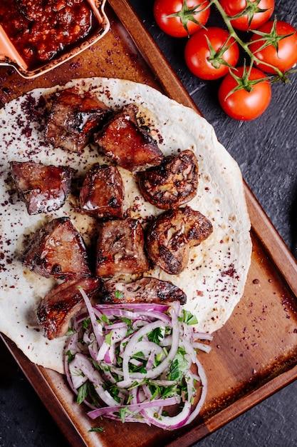 Espetada de carne do azerbaijão no pão de lavash com salada de cebola e molho de churrasco. Foto gratuita
