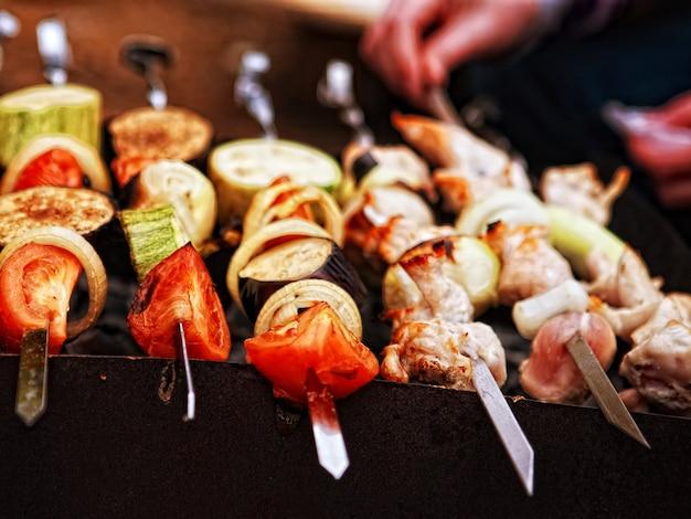 Espetada de carnes e legumes cozinhar na grelha Foto Premium