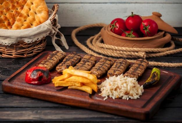 Espetadas de carne com arroz, batatas fritas, tomate e pimentão grelhado Foto gratuita
