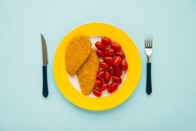 Espetinho de frango e tomate pequeno na placa amarela Foto gratuita