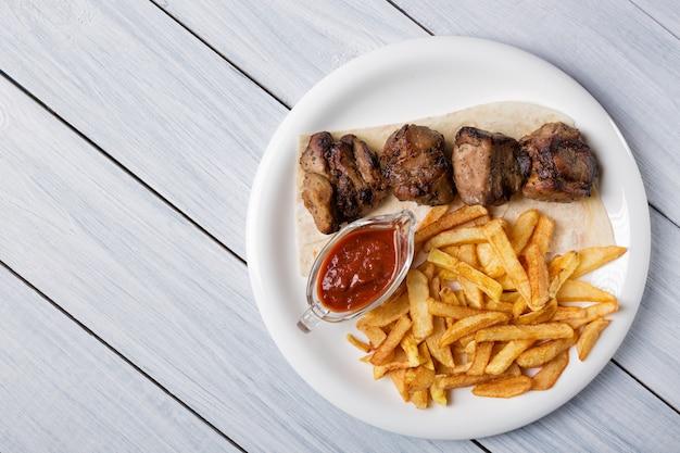 Espetinho grelhado servido com batatas fritas e molho na mesa de madeira branca Foto Premium