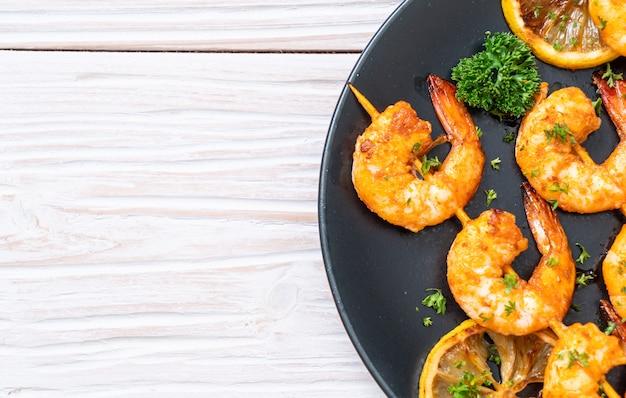 Espetos de camarão tigre grelhado com limão Foto Premium