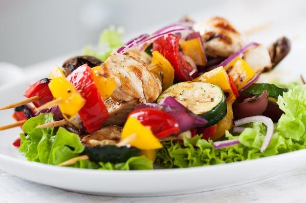Espetos de frango com cebolas em cima de uma salada Foto gratuita