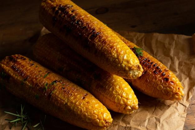 Espigas de milho grelhadas no fundo de madeira. Foto gratuita