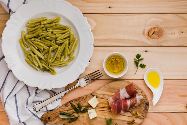 Espinafre massa gemelli; queijo; bacon e óleo infundido na mesa de madeira Foto gratuita