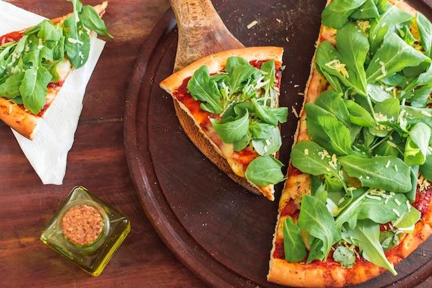 Espinafre na fatia de pizza sobre a bandeja circular de madeira Foto gratuita