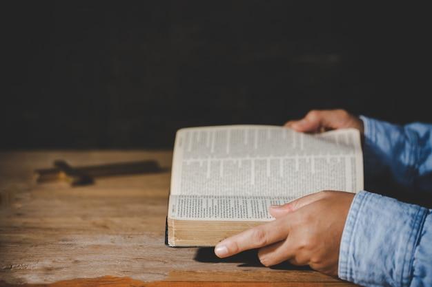 Espiritualidade e religião, as mãos postas em oração sobre uma bíblia sagrada na igreja conceito de fé. Foto gratuita