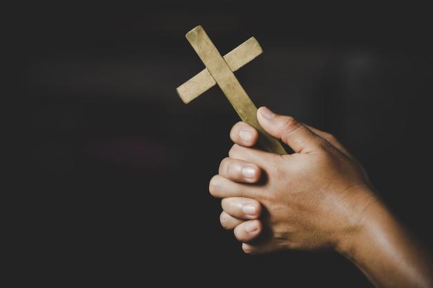 Espiritualidade e religião, mulheres em conceitos religiosos mãos que praying ao deus ao prender o símbolo da cruz. freira pegou a cruz na mão. Foto gratuita
