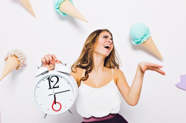 Esplêndida jovem em um top branco posando com os olhos fechados, segurando o relógio na parede decorada. retrato de menina morena animada rindo em frente a parede com doces de brinquedo nele. Foto gratuita