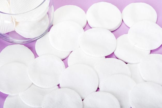 Esponja de algodão em um fundo rosa com um frasco de vidro Foto Premium