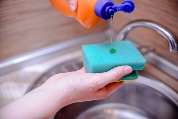 Esponja de prato com sabão de lavar louça. conceito de limpeza da casa. Foto Premium