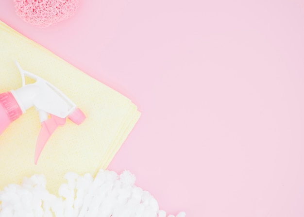 Esponja; frasco de spray e guardanapo no pano de fundo rosa Foto gratuita