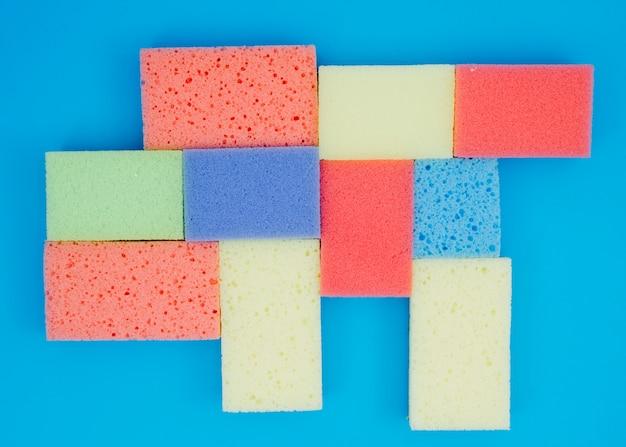 Esponjas coloridas em fundo azul Foto gratuita