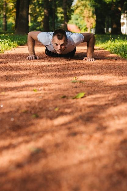 Esporte homens fazendo flexões durante treino cruzado ao ar livre no parque Foto Premium