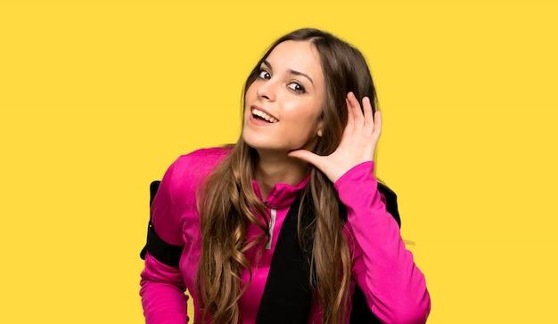 Esporte jovem mulher ouvindo algo, colocando a mão na orelha Foto Premium