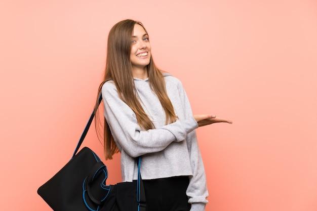 Esporte jovem mulher rosa estendendo as mãos para o lado para convidar para vir Foto Premium