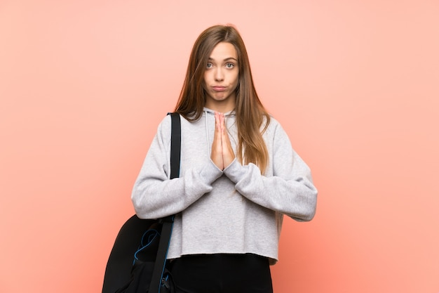 Esporte jovem mulher sobre fundo rosa isolado suplicando Foto Premium